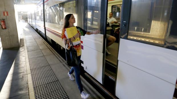 Una chica accede a un vagón del tren que va al Campus de Rabanales