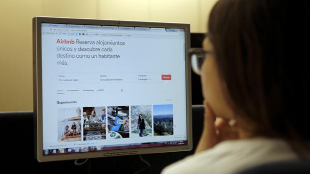 Una joven consulta una página de apartamentos turísticos