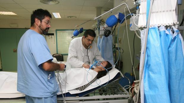 Un doctor y un enfermero atienden a una paciente en el hospital Reina Sofía de Córdoba