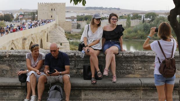 Dos turistas se fotografían con el Puente Romano y la Torre de la Calahorra, al fondo
