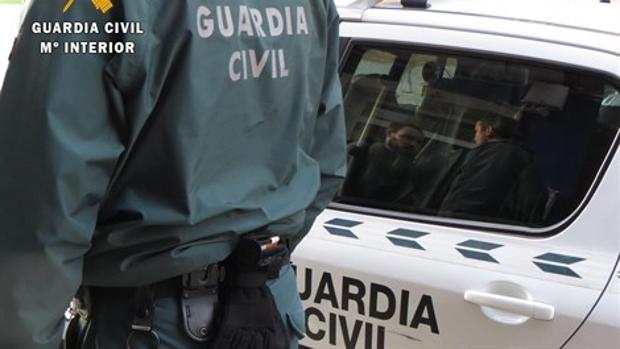 Imagen de archivo de un agente y un vehículo de la Guardia Civil.