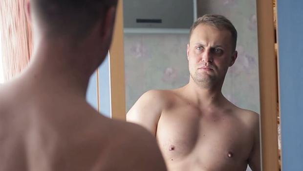 Imagen de archivo de un hombre mirándose en el espejo.