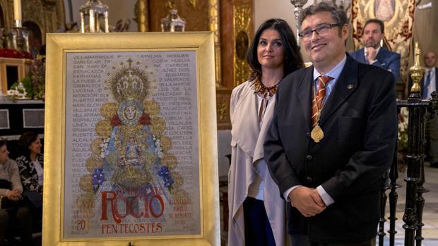 Autora y presidente de la Matriz posan ante la obra que servirá para anunciar la Romería del Rocío del 2019