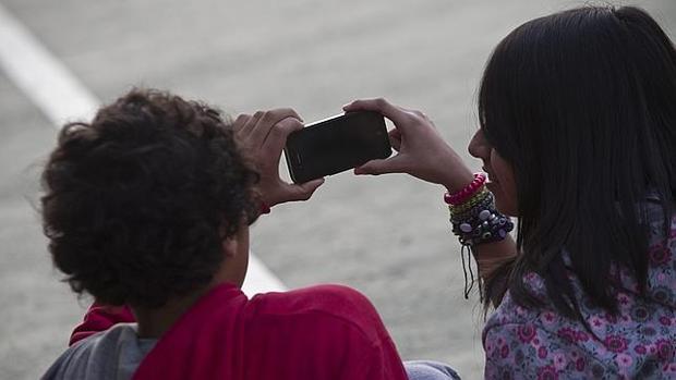 Dos jóvenes juegan con un teléfono móvil