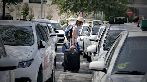 Una clienta bordea los taxis de la estación de Santa Justa, durante una de las huelgas del sector