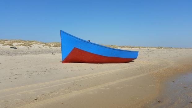 La patera encallada en la costa de Matalascañas a mediodía de este domingo