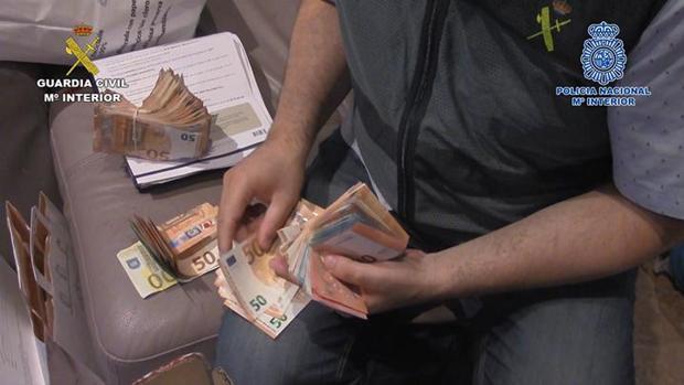 Un agente de la Guardia Civil cuenta dinero requisado al grupo criminal