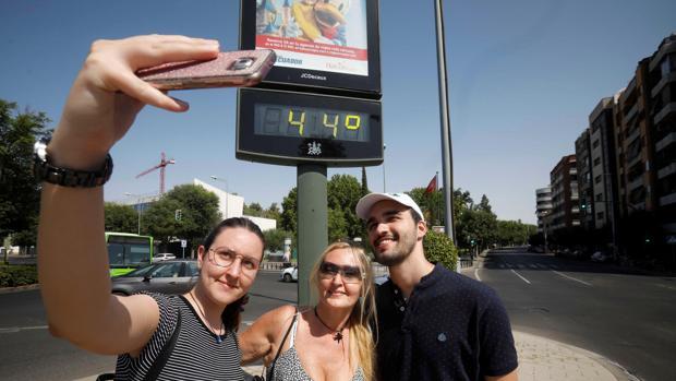 Unos turistas se fotografían con un termómetro del centro de Córdoba que indica 44 grados