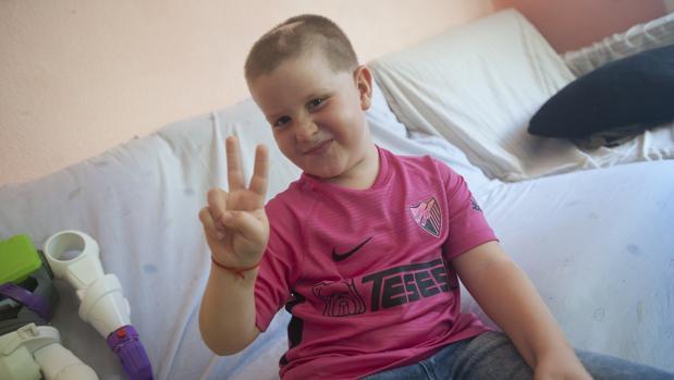 Cristian en su casa con la camiseta que le han regalado los jugadores del Málaga C. F.