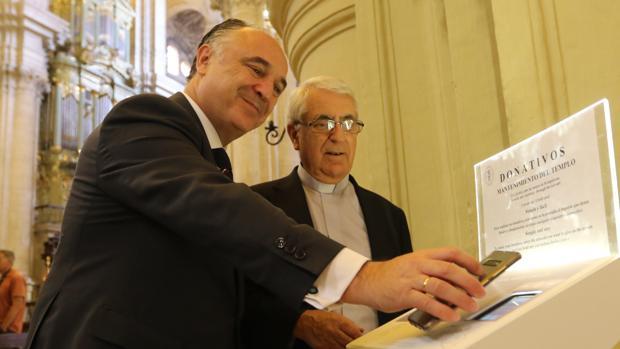 El director territorial de CaixaBank en Andalucía Oriental y Murcia, Juan Ignacio Zafra, y el deán de la Catedral, Antonio Aguilera, prueban uno de los cepillos