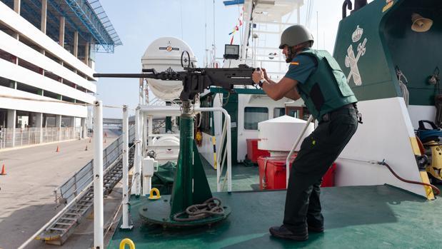Un agente de la tripulación del «Río Miño», con una de las armas del buque