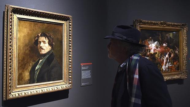 Un hombre admira el autorretrato de Delacroix, que cuelga en la exposición