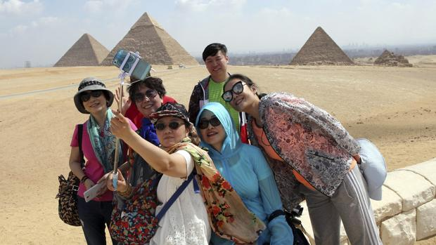 Un grupo de turistas se hace un selfie frente a las pirámides de Guiza, en Egipto