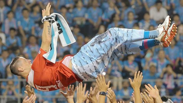 Torres, manteado en por sus compañeros del Sagan Tosu tras el partido