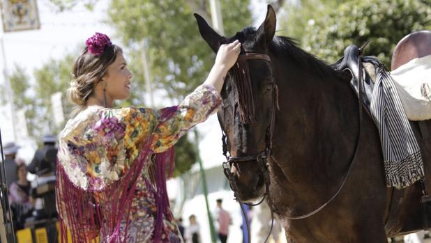 Una chica vestida de gitana acaricia las crines de un caballo