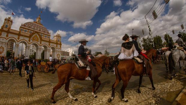 Caballistas en la calle Antonio Bienvenida, ante la portada de Feria