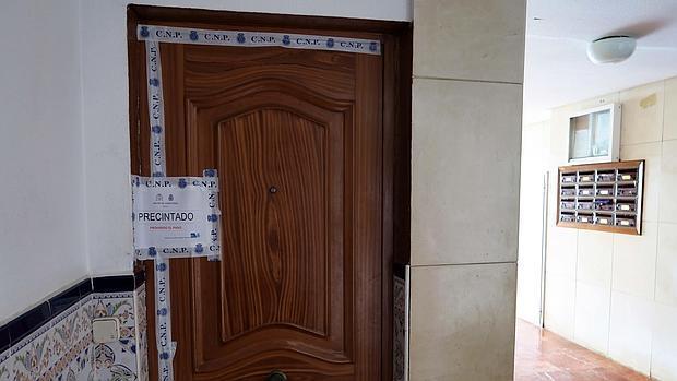 Puerta de acceso al piso de la barriada de Los Prunos donde falleció el bebé de año y medio