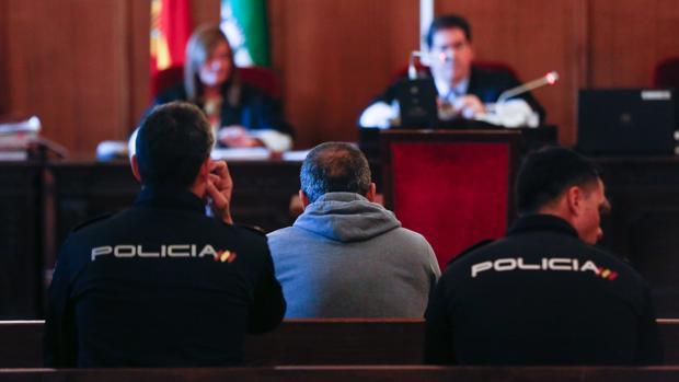 El acusado, escoltado por la Policía en el banquillo de la sala donde está siendo juzgado