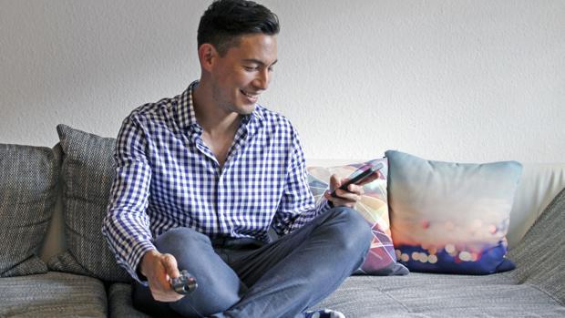 Un joven usando el teléfono móvil como entretenimiento