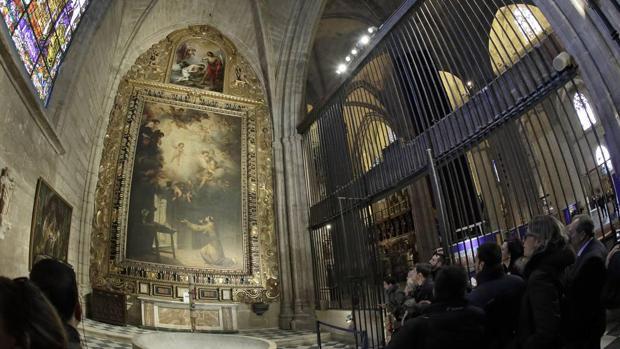 Algunos visitantes observan el cuadro «La visión de San Antonio de Padua» en la Capilla Bautismal de la Catedral
