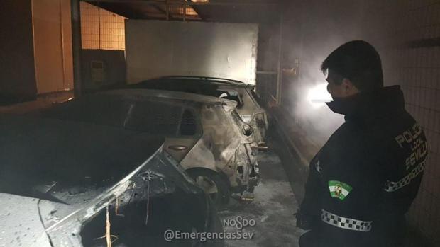 Un agente de la Polícia Local de Sevilla observa los vehículos calcinados