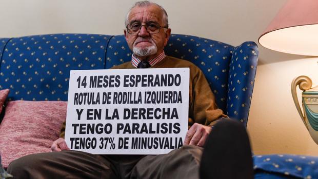 Ricardo Bernal en su casa con un cartel en el que detalla su situación