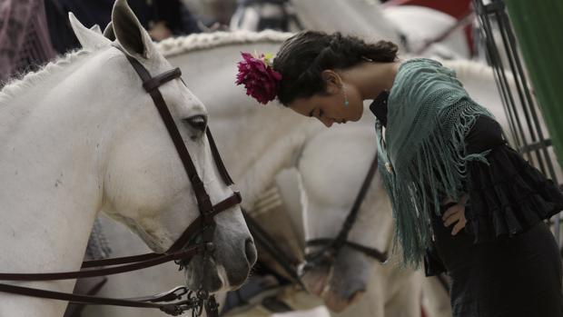 Una joven vestida de flamenca, junto al paseo de caballos